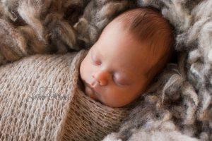 Newborn waarvan alleen het hoofdje nog zichtbaar is, slapend onder bruine deken.