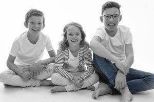 Portretfotografie gezin lachende kinderen met accent op blauwe broek.