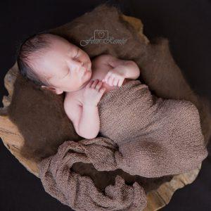 Newborn slapend in houten schaal