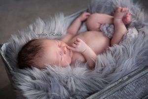 Baby slaapt heerlijk op een grijs deken. Nu bij een fotoshoot een gratis mini-album