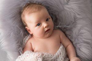 Newborn net wakker op grijze deken