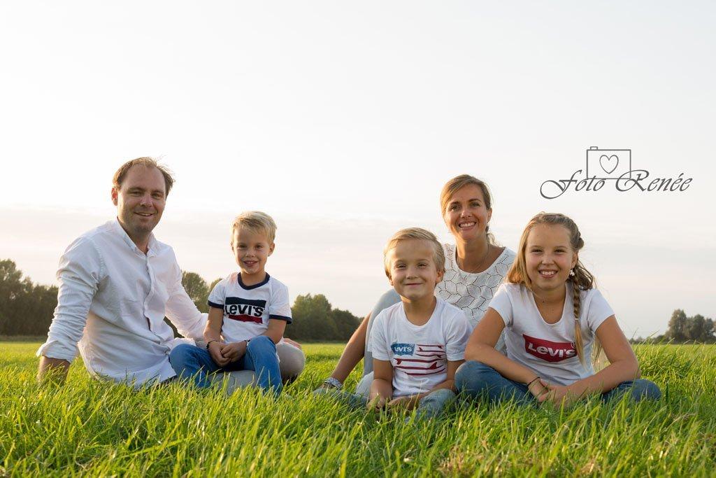 Familie zit lekker in het zonnetje in het gras. Nu 50% cadeau! Leuk voor bijvoorbeeld kerst!