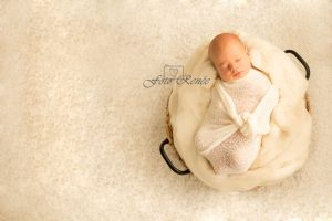 pasgeboren baby slaapt heerlijk in een witte wrap in een mandje met witte wol