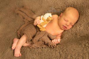 Newborn babyjongen slaapt op een bruin deken