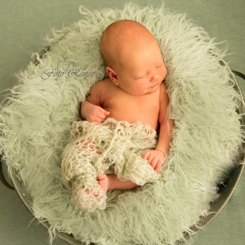 Nieuw leven. Baby slaapt op een groen fluffy kleed