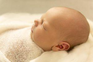 Newborn jongen slaapt op een wit kleed