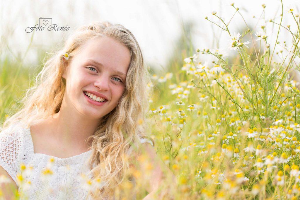 portret van een mooi meisje tussen de bloemen