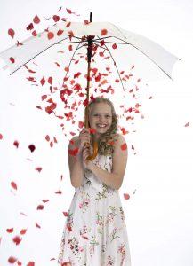 Meisje onder paraplu met witte rozen