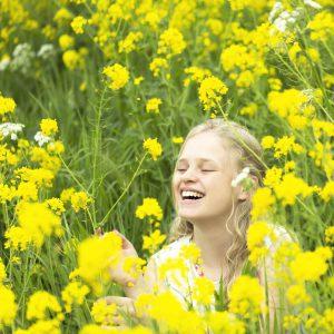 Blond meisje in een bloemenveld