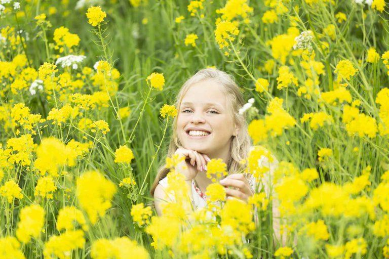 Blond meisje tussen gele bloemen